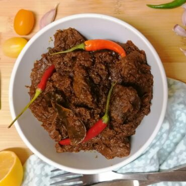 A bowl of Indonesian beef rendang with three chillies as garnish