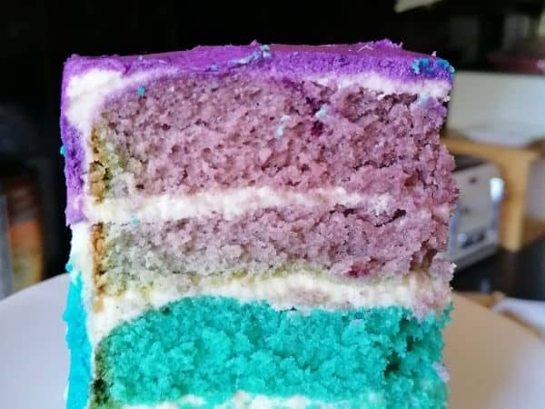 A slice of vanilla velvet cake in turquoise and purple colours