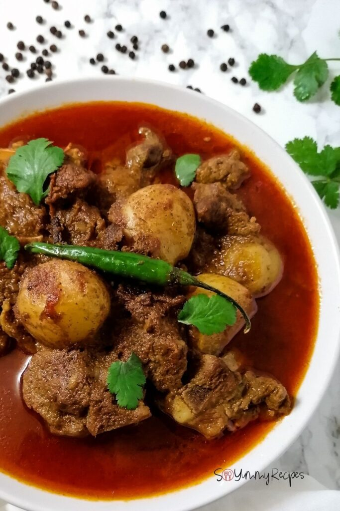 aloo gosht - Pakistani lamb meat and potato curry in a white bowl with sprinkles of black pepper and coriander in the background
