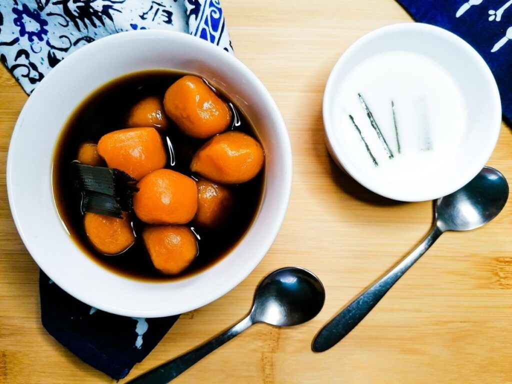a bowl of sweet potato balls and a bowl of coconut milk with two dessert spoons