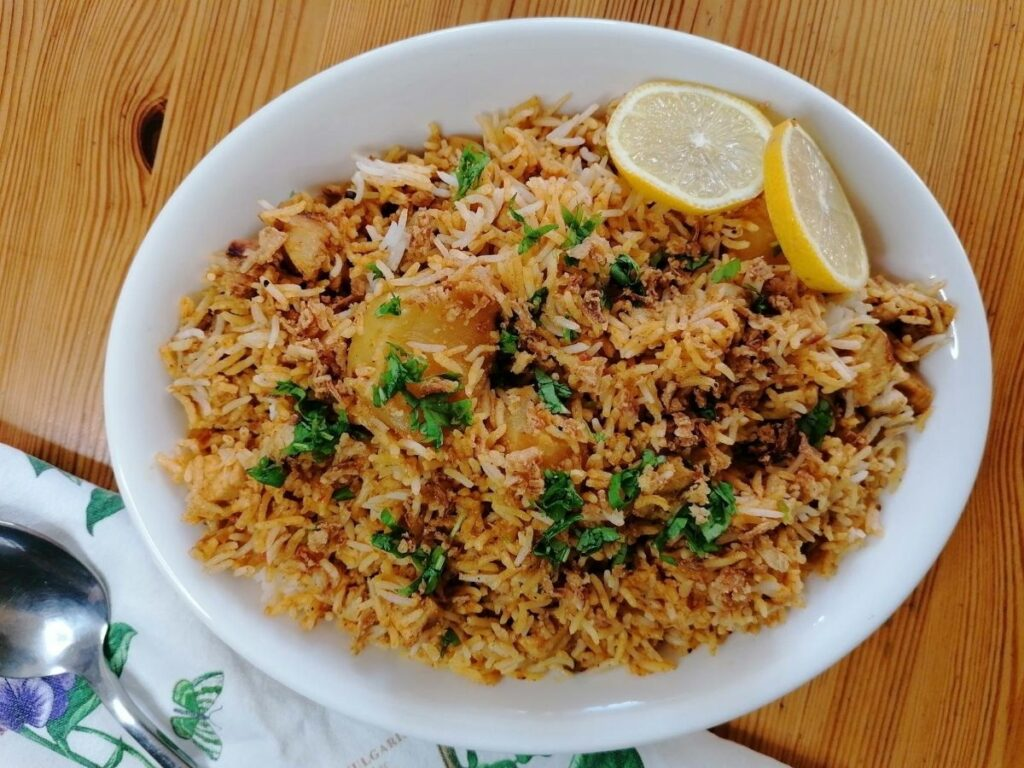 chicken biryani rice garnished with coriander leaves and lemon slices