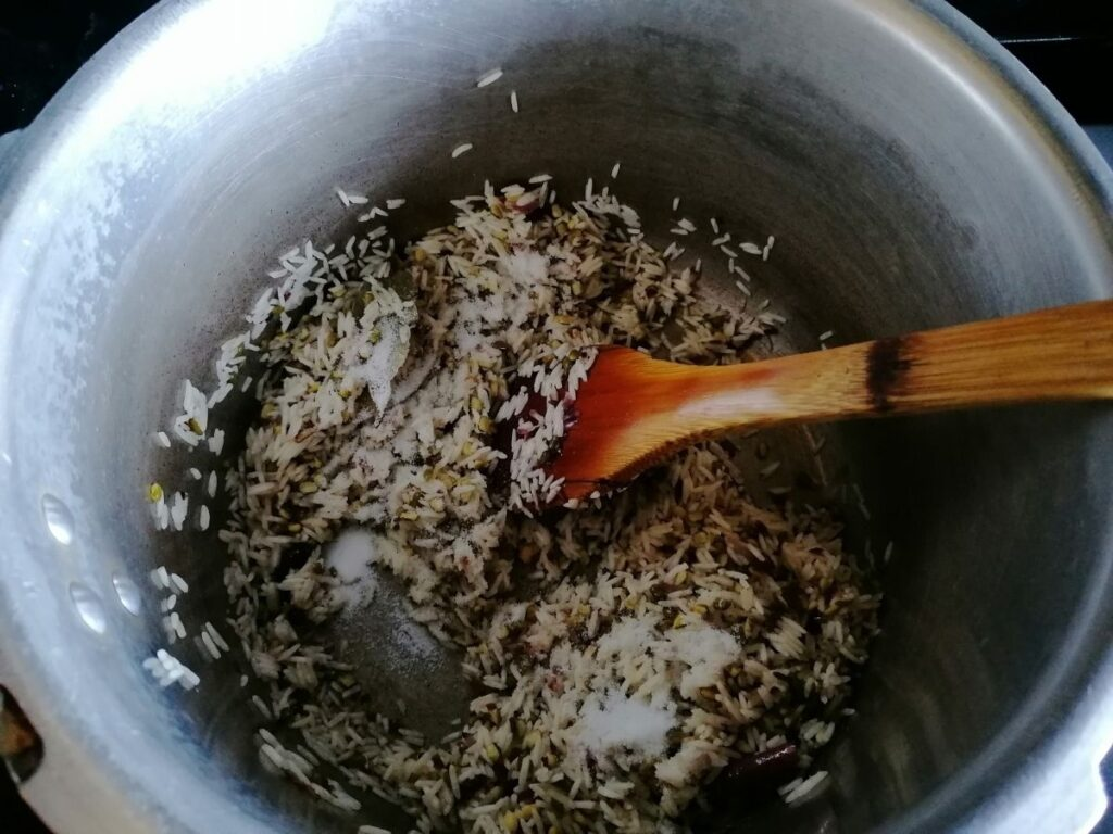 frying the rice, mung beans, and spices to make kitchari