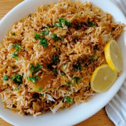 a platter of chicken biryani rice with two slices of lemon