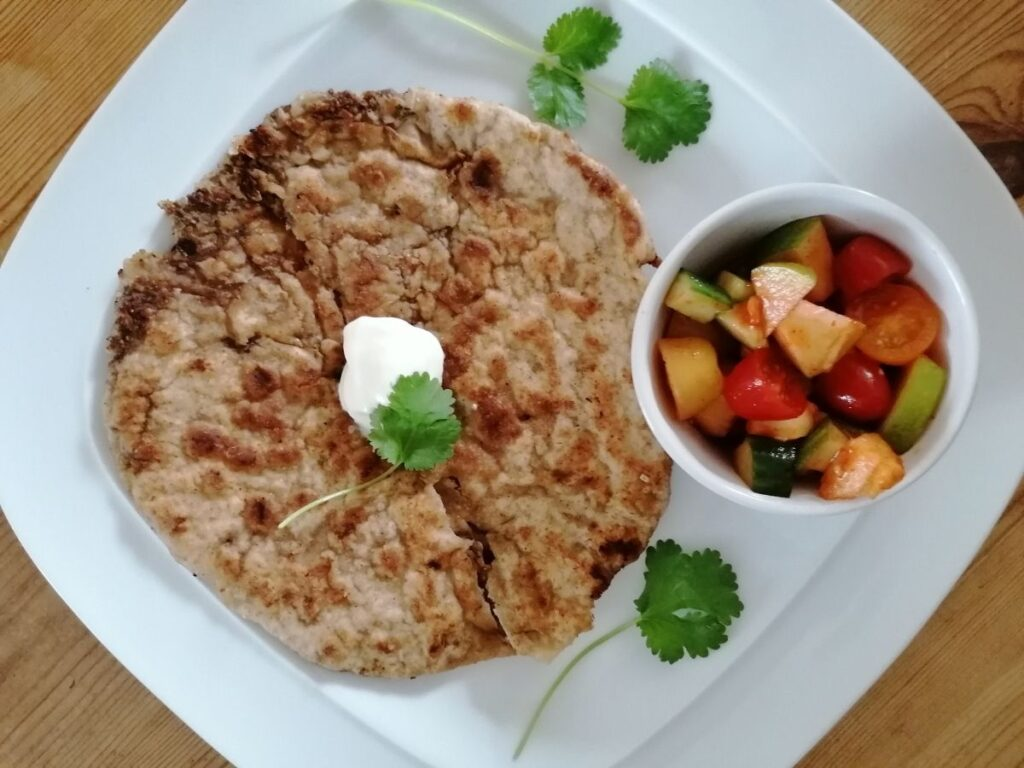 Keema Paratha with a dollop of yoghurt and a small bowl of tomato salad