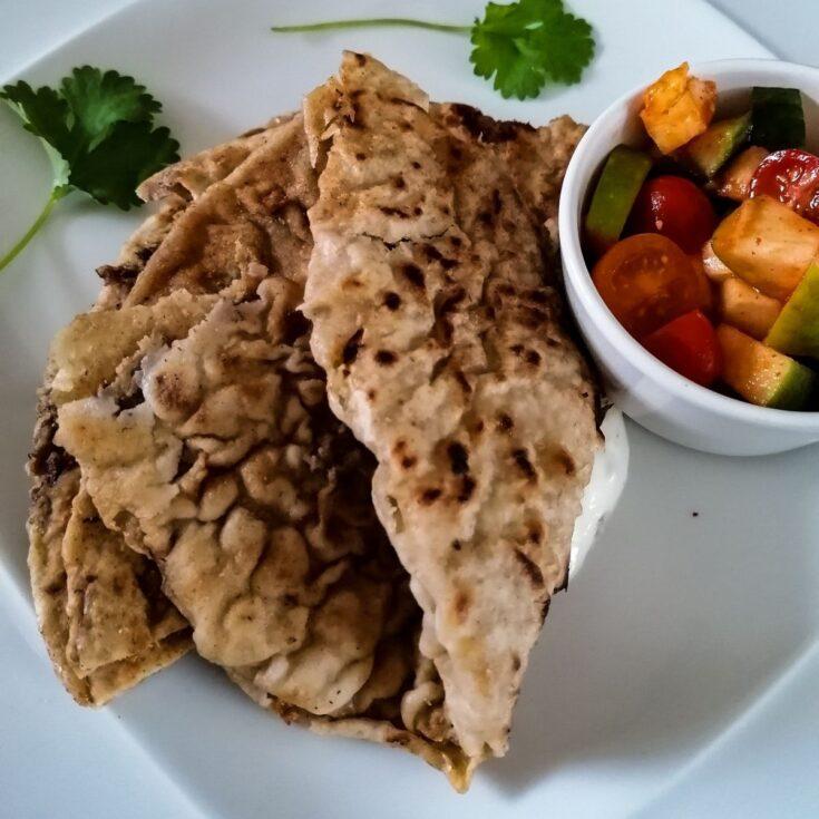 Keema Paratha - Pakistani stuffed flatbread with a bowl of tomato salad