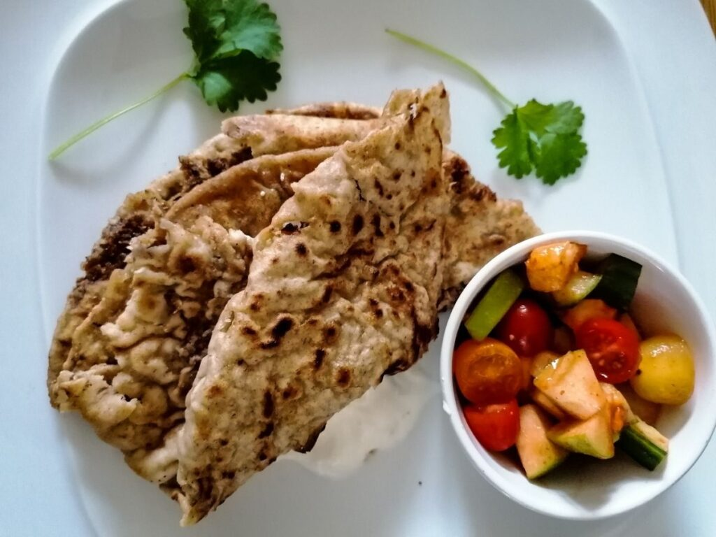 Flatbread with minced meat filling - keema paratha with a bowl of tomato salad