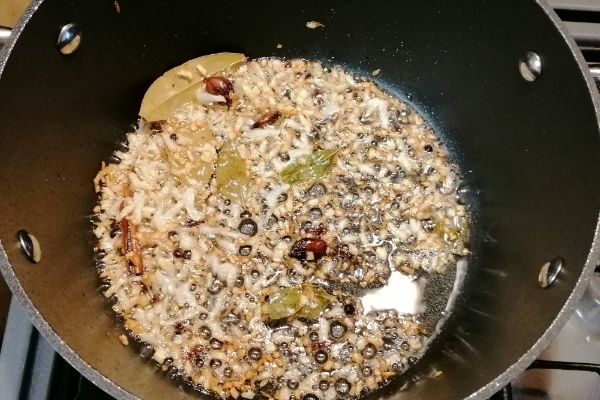 onion and spices being fried on a cooking pan