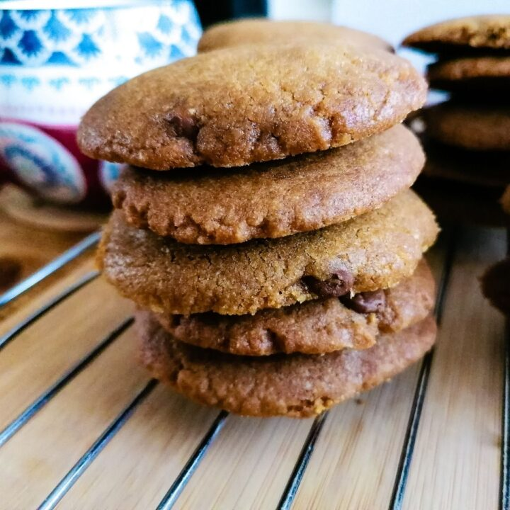 a stack of chocolate chip cookies with coconut oil on a cooling rack