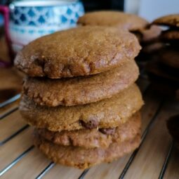 chocolate chip cookies with coconut oil stacked up on a cooling rack