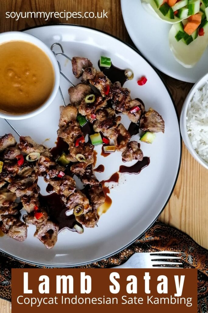 a plate of meat skewers with a bowl of peanut sauce with an overlay text