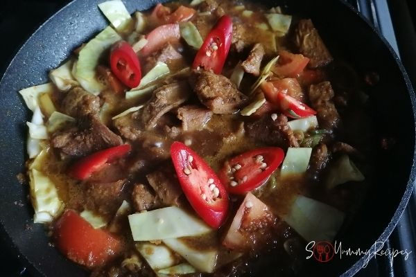 adding chillies and sweet soy sauce to braised lamb