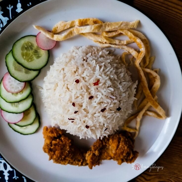 a plate of nasi uduk, cucumber, omelette, and fried chicken
