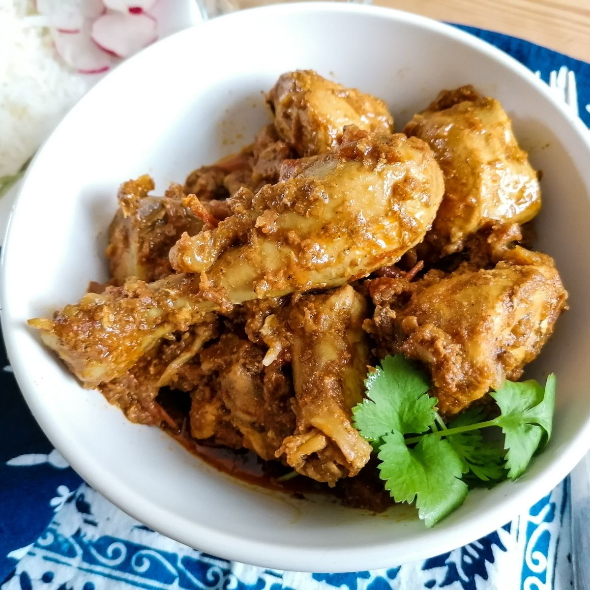 Chicken Karahi Pakistani style in a white bowl with coriander leaves garnish
