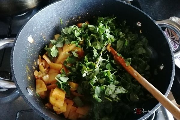 adding fenugreek leaves into potato curry