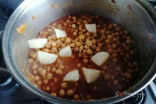 adding potatoes into the chickpea curry