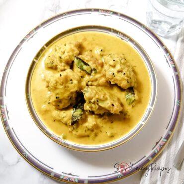 a bowl of kadhi pakora - pakistani dumplings in yoghurt sauce