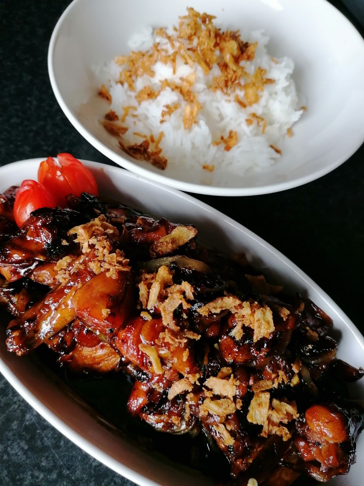 A dish of sweet soy sauce chicken and a bowl of white rice