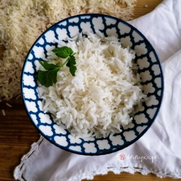a bowl of basmati rice garnished with coriander leaves with a white napkin under the bowl and some raw rice grains near the bowl