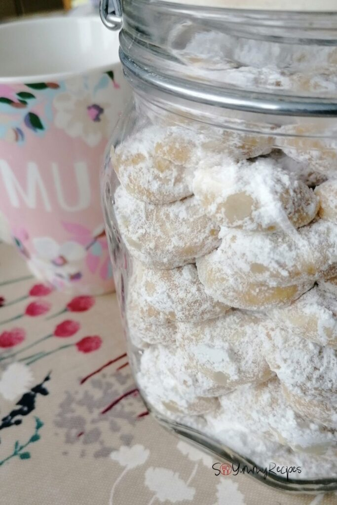 a jar of kue putri salju - Indonesian Snow White Butter Cookies - with a pink mug next to the jar