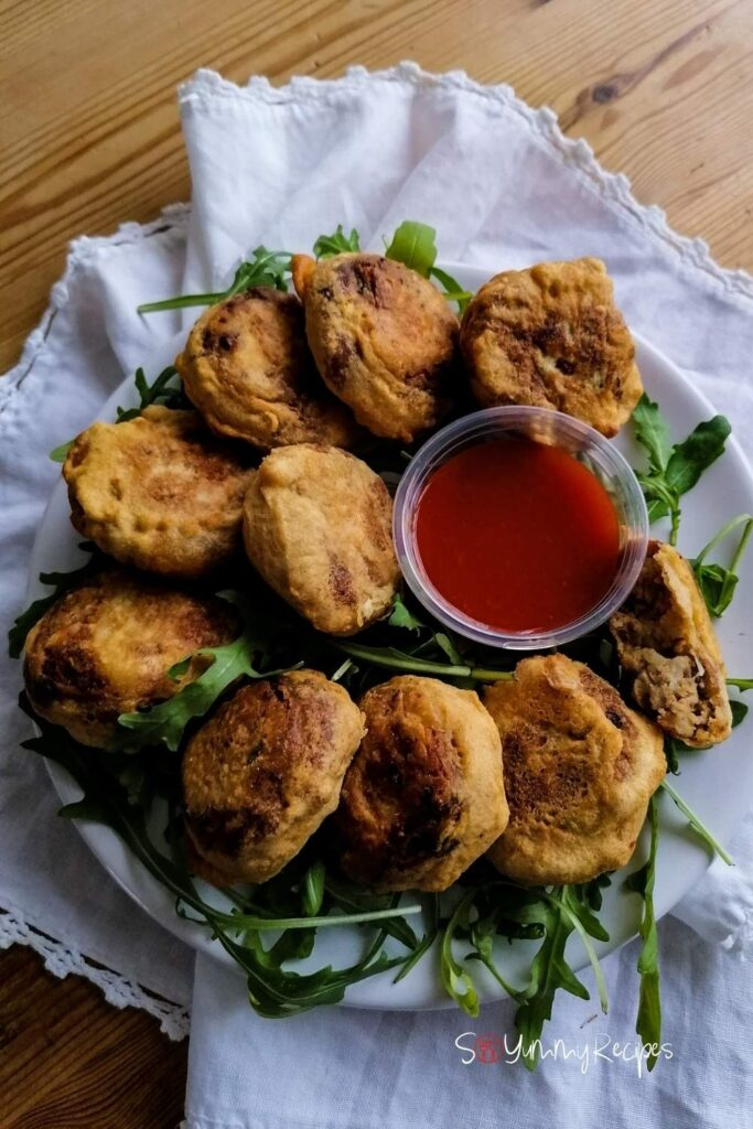 A plate of Pakistani Aloo Tikki with a small bowl of chilli sauce and some rocket leaves