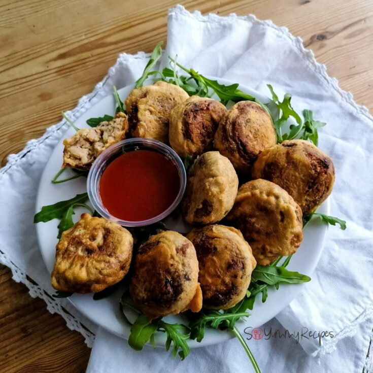 a plate of Pakistani Aloo Tikki on a white napkin with a small bowl of chilli sauce and some rocket leaves.