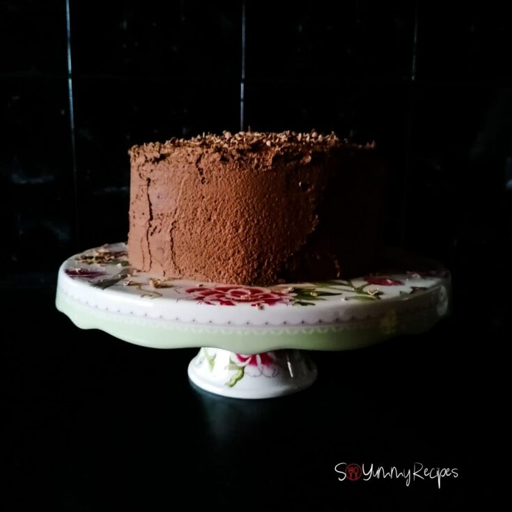 chocolate cake with chocolate mousse frosting on a white cake stand with black tile background