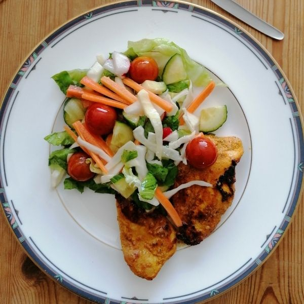 a plate of chicken tikka garnished with crunchy salad