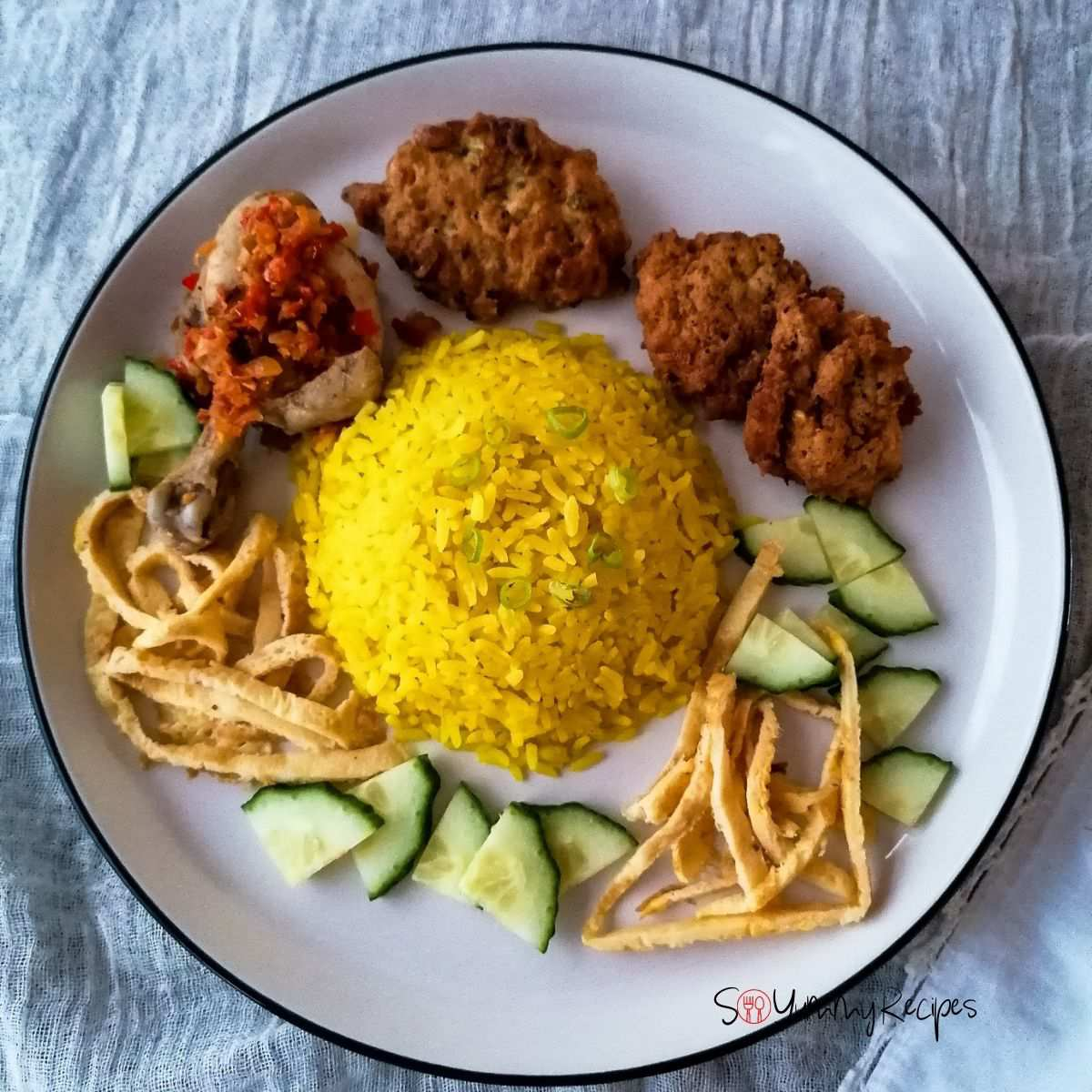 A plate of Nasi Kuning - the Indonesian yellow rice surrounded with chicken, fritters, slices of omelettes and cucumber