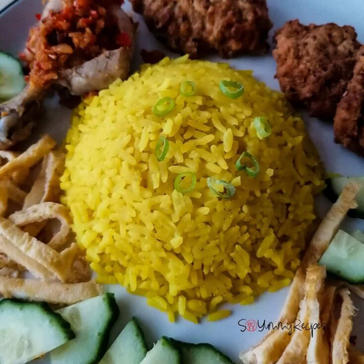 Nasi Kuning - the Indonesian yellow rice with some fritters, chicken, slices of egg omelettes, and cucumber