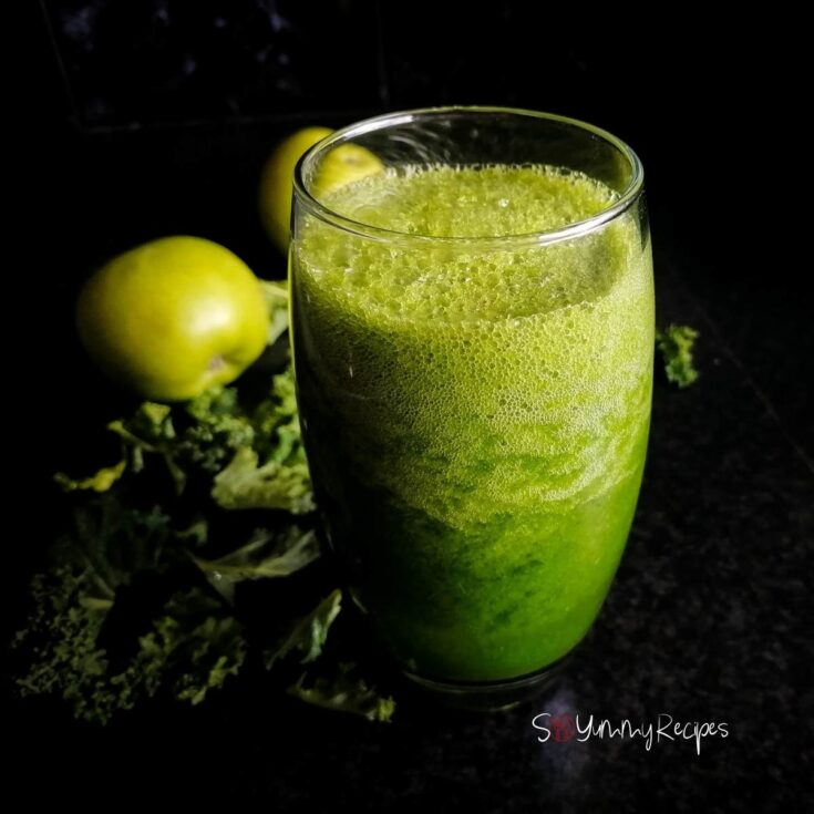 Apple and kale smoothie in a tall glass with apple and kale in the background