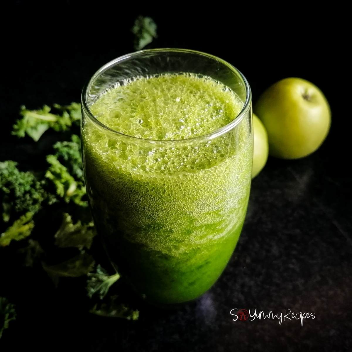 a glass of green apple and kale smoothie with apples and some kale leaves on the background