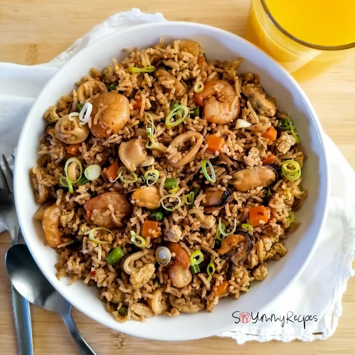 Nasi Goreng Seafood Recipe Indonesian in a white plate with a glass of orange juice on the side