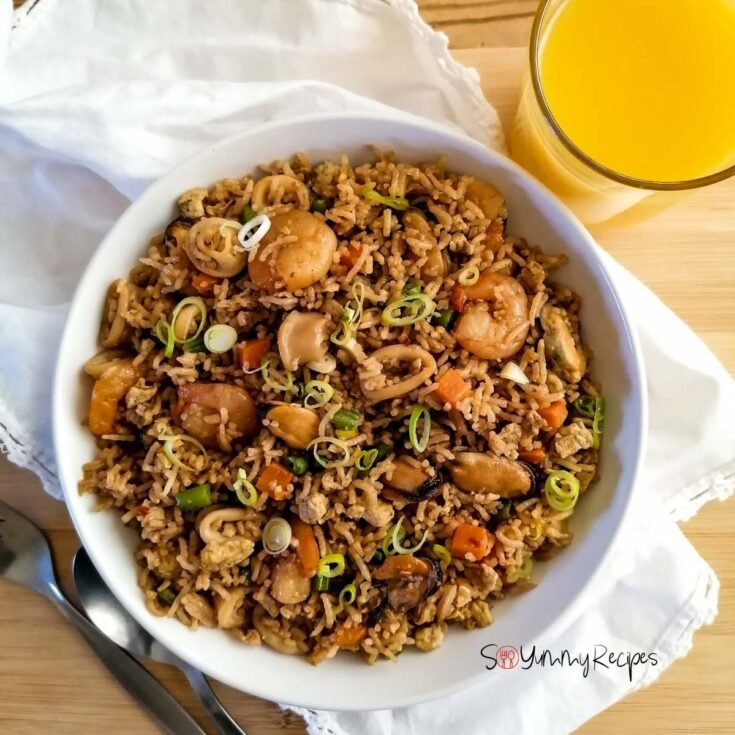 A bowl of Indonesian Nasi Goreng Seafood Recipe with a glass of orange juice and white napkin
