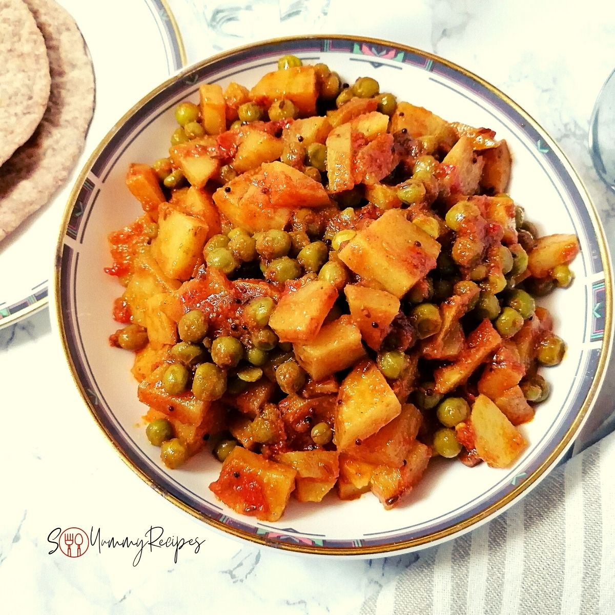 Aloo Matar - the Pakistani potato and green peas curry in a round dish