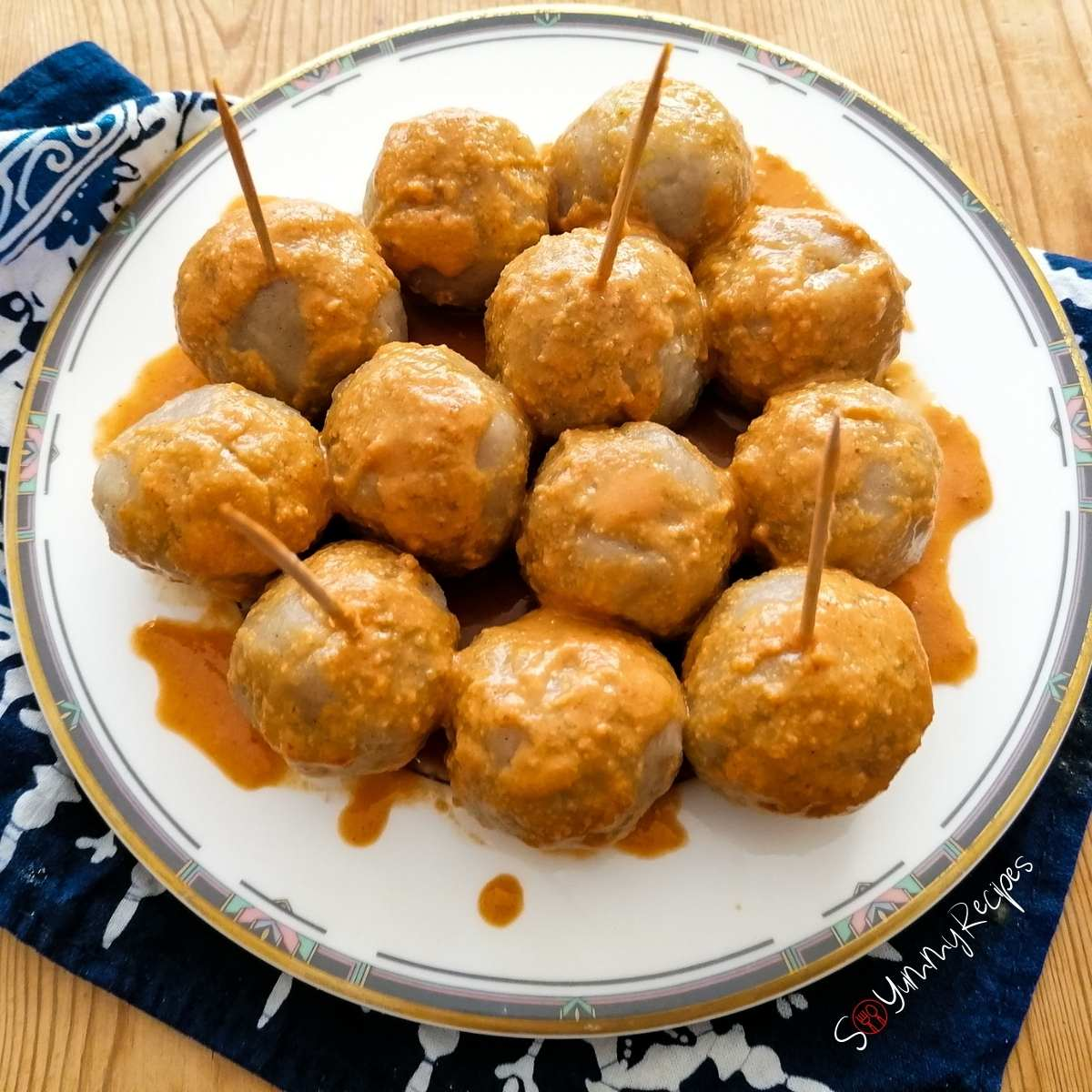 a plate of Cilok - Indonesian tapioca balls drizzled with spicy peanut sauce