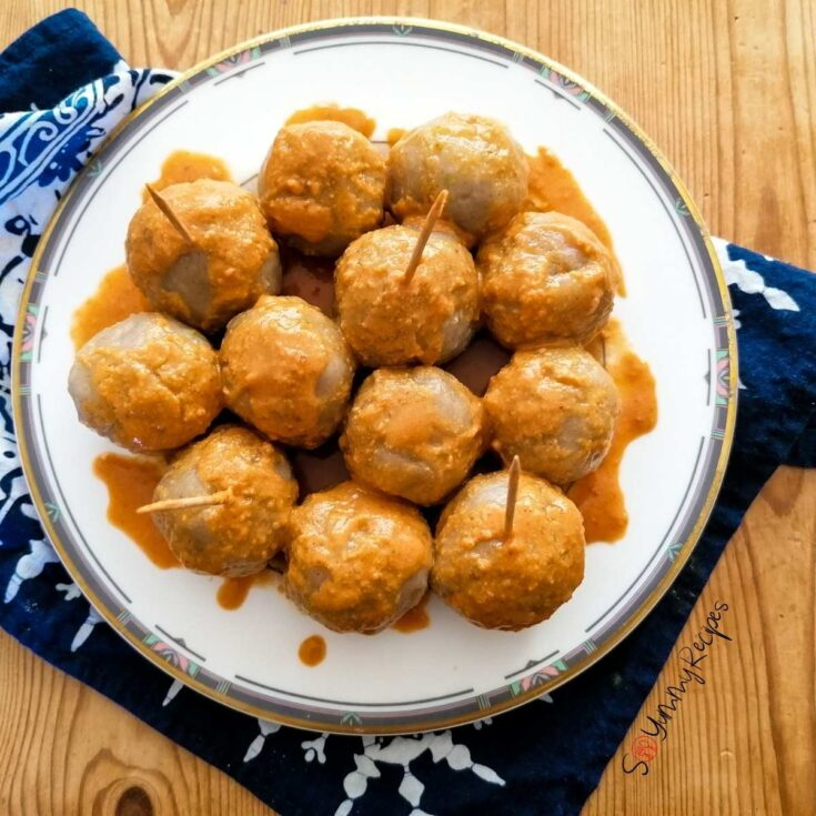 Cilok - Indonesian tapioca dumpling balls - drizzled with spicy peanut sauce on a white plate