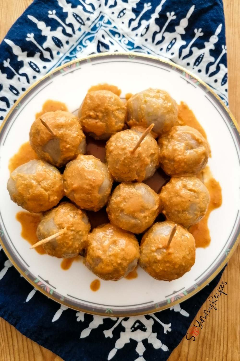 15 balls of Cilok - the chewy tapioca dumplings - on a white plate drizzled with spicy peanut sauce.