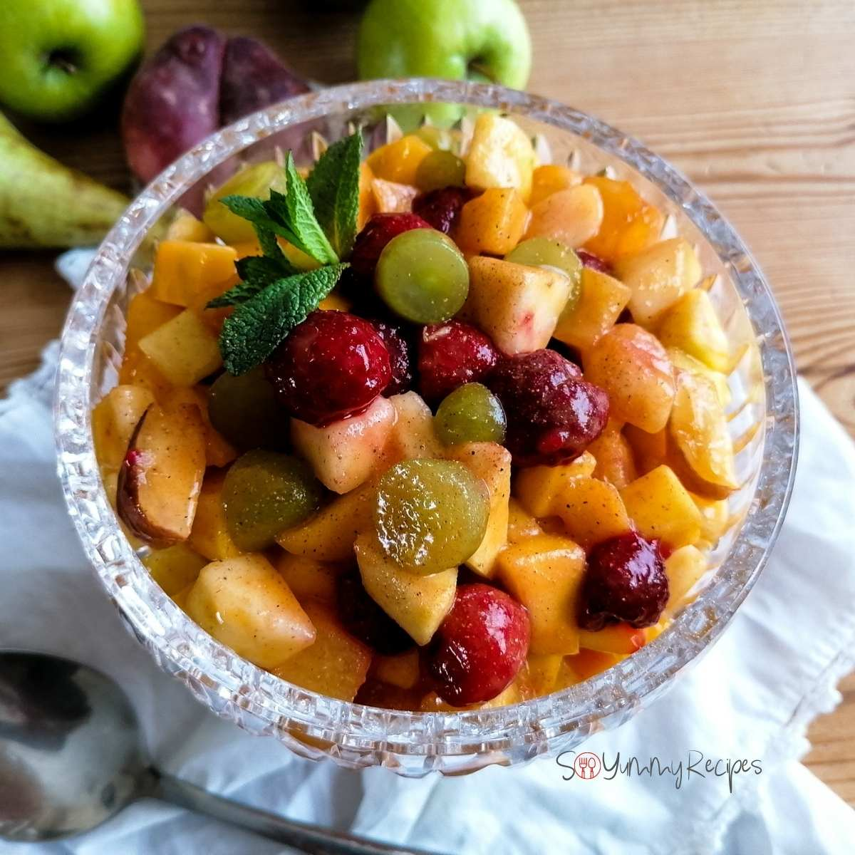 Pakistani style fruit chaat in a crystal bowl with white napkin, a spoon and some fruits on the background