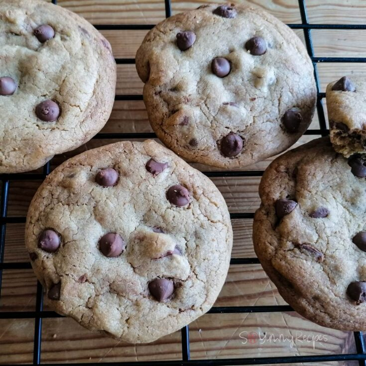 four chewy chocolate chip cookies on a cooling rack