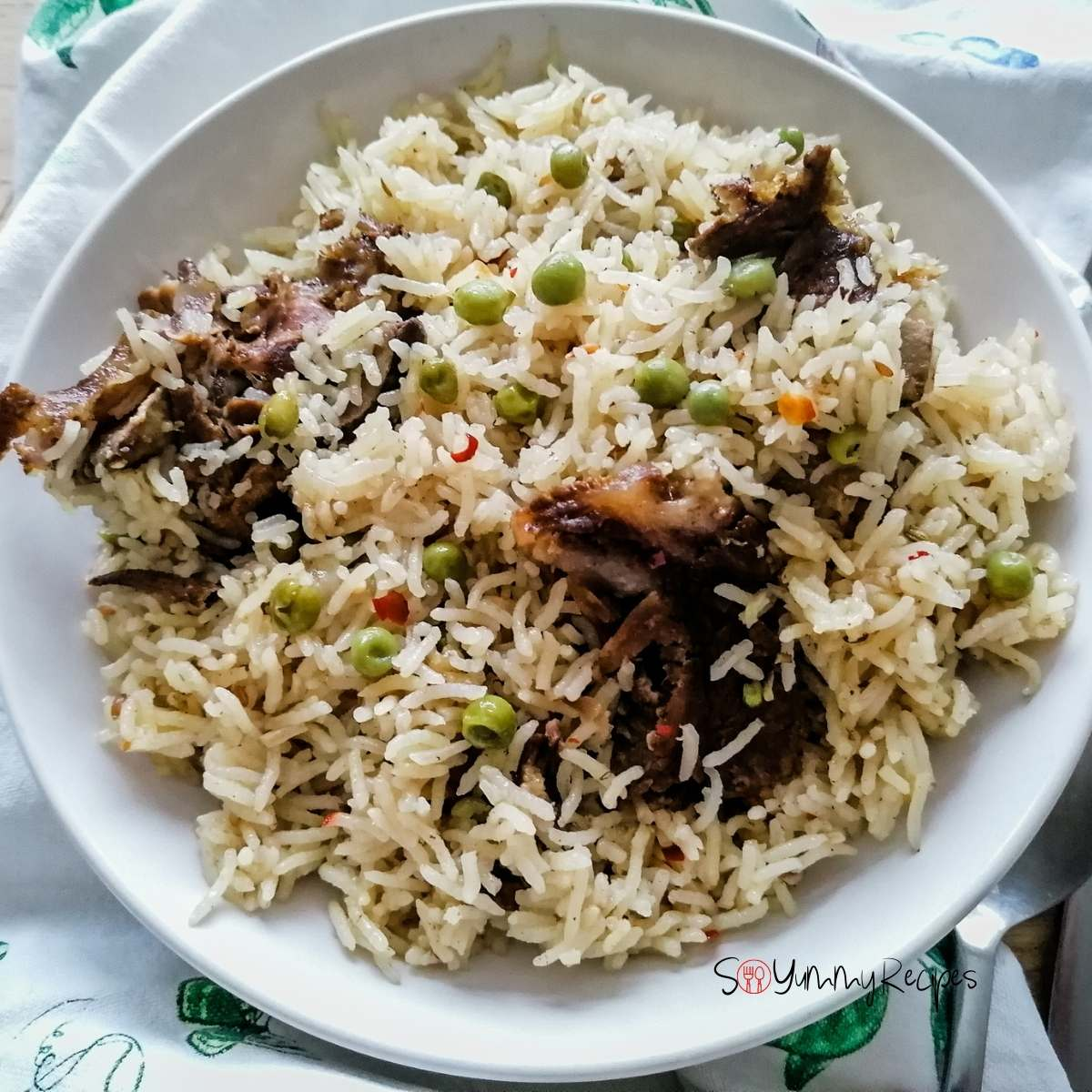 A white plate of Yakhni mutton pulao rice with green peas.