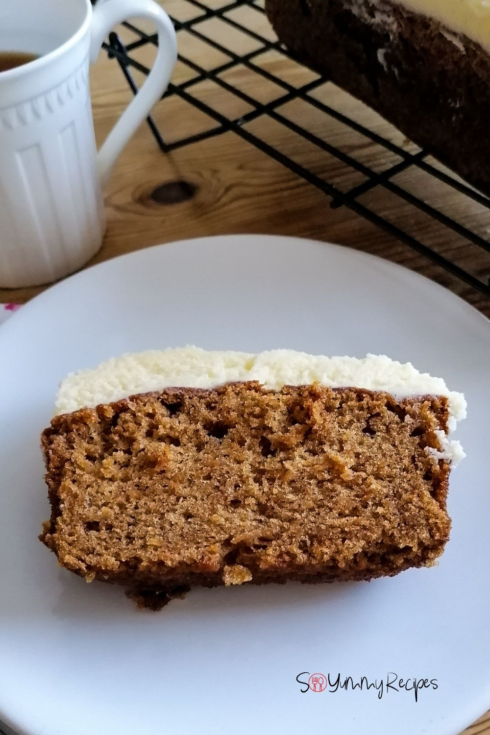 a slice of carrot cake on a white plate with a white mug on the side