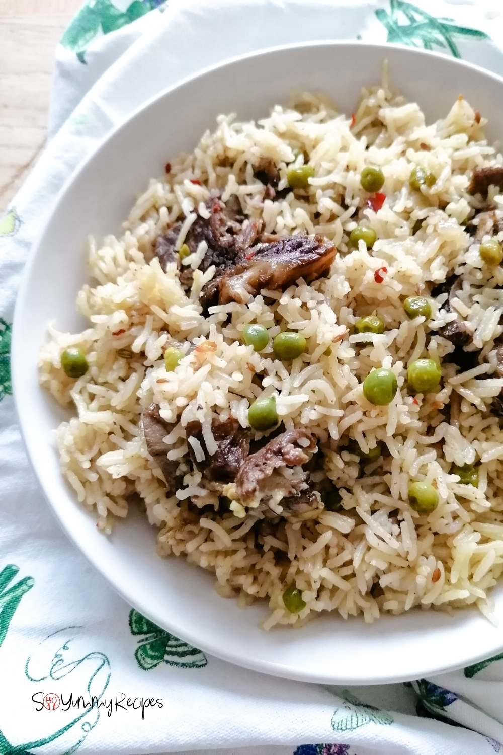 Pakistani Yakhni mutton pulao rice on a white plate with patterned white napkin underneath.