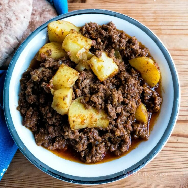Pakistani aloo keema - the potato and minced meat curry - in a round white dish.