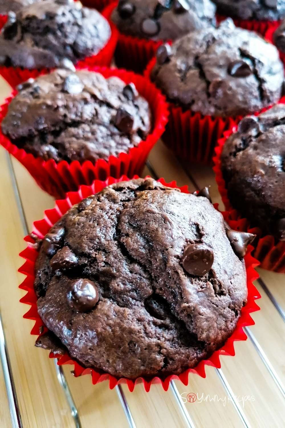 Double chocolate muffins in red paper muffin cases on a wire cooling rack.