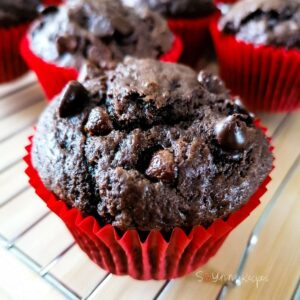 A double chocolate chip muffin on a red muffin case on a cooling rack with a few other muffins in the background.